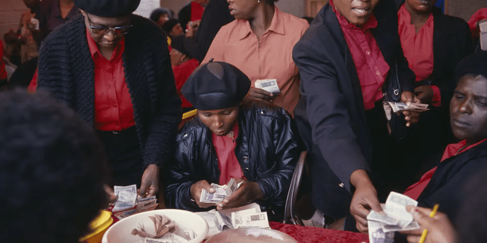 Women belonging to a savings club - Stokvel / Round / Mukando counting handing each other and counting money.